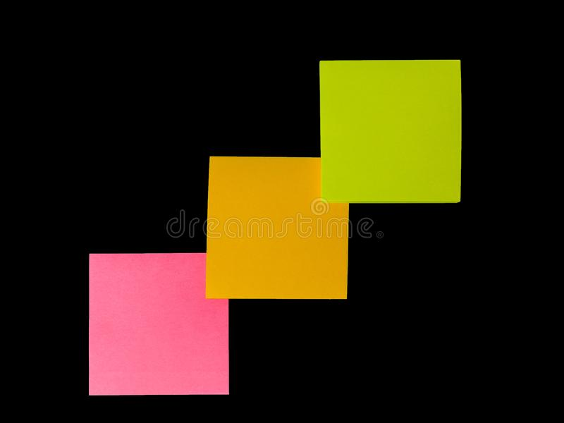 Nota de los posts o post-it anaranjada, rosada, verde en fondo negro imagen de archivo