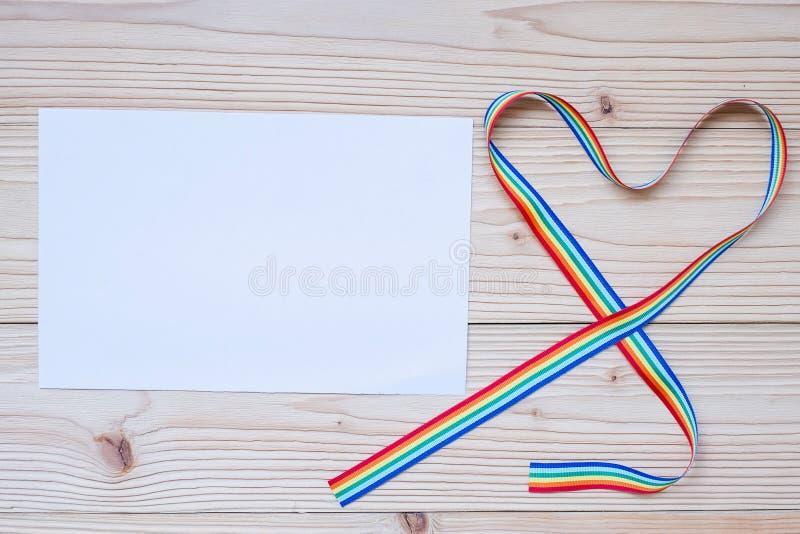 Nota de papel en blanco para LGBTQ con la cinta del arco iris de la forma del corazón para lesbiano, homosexual, bisexual, el tra foto de archivo