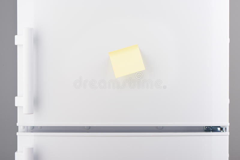 Nota de papel pegajosa amarilla clara en blanco sobre el refrigerador blanco fotografía de archivo