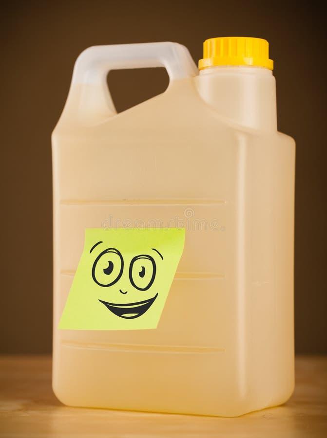 A nota de post-it com cara do smiley sticked no galão fotografia de stock