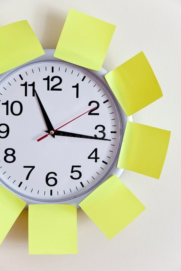 Nota del reloj y del pegamento foto de archivo