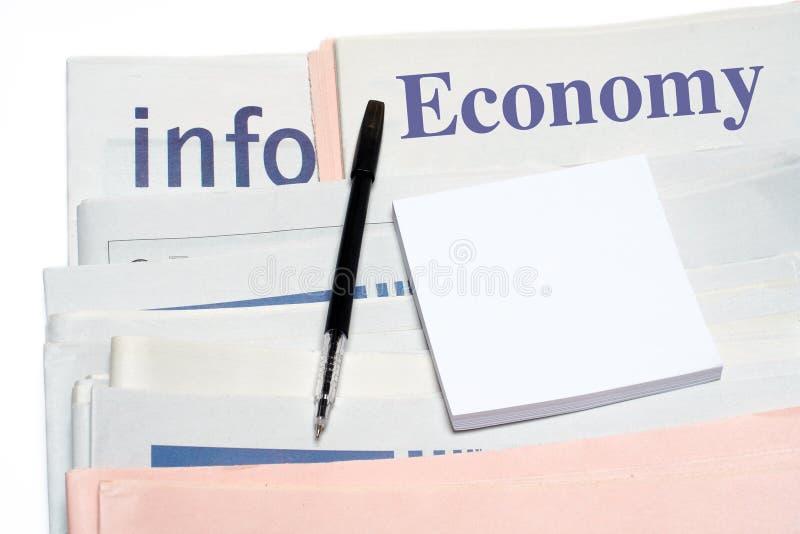 Nota e pena, sobre jornais empilhados da economia fotografia de stock