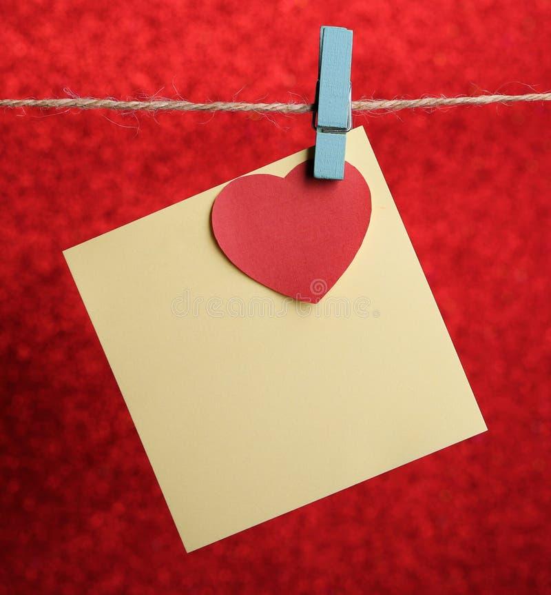 Nota en blanco con el corazón rojo contra fondo rojo fotografía de archivo libre de regalías
