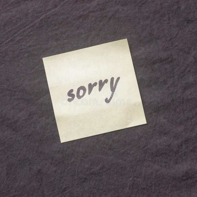Nota escrita à mão em um fundo escuro Nota de desculpa pesarosa, p foto de stock