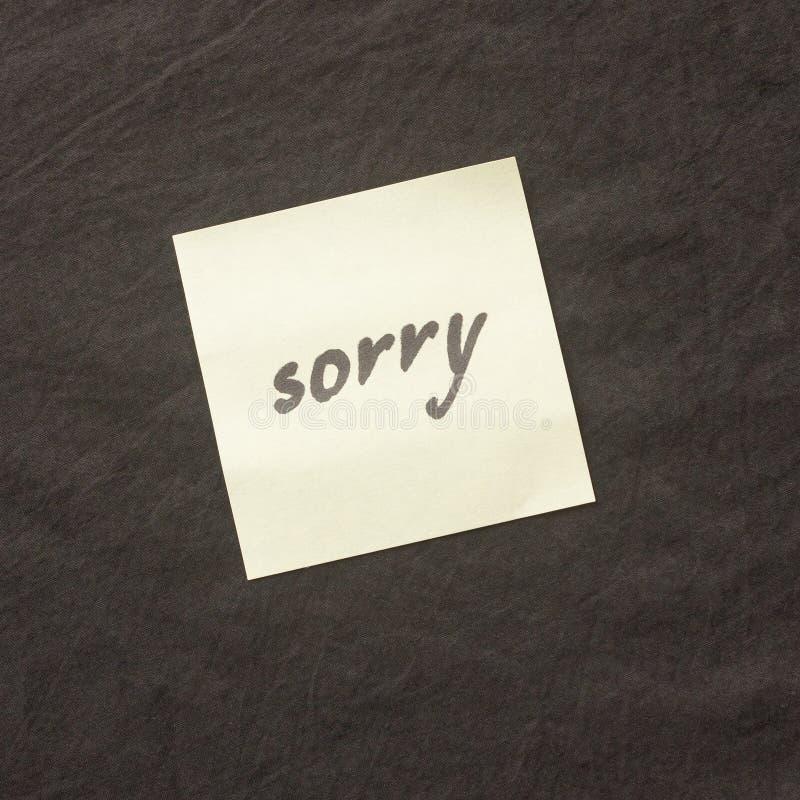 Nota escrita à mão em um fundo escuro Nota de desculpa pesarosa, p fotos de stock