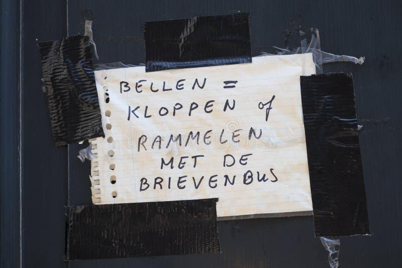 Nota escrita impar sobre una puerta principal imagen de archivo