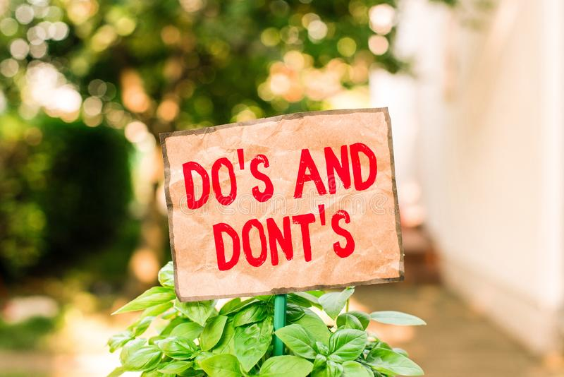 Nota escrita que muestra Do S And Dont S. Fotos comerciales que muestran las normas o costumbres relativas a algunas actividades o foto de archivo libre de regalías