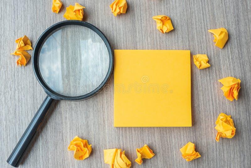 Nota gialla vuota con carta e la lente d'ingrandimento sbriciolate sul fondo di legno della tavola Idea, visione, soluzione, stra fotografia stock libera da diritti