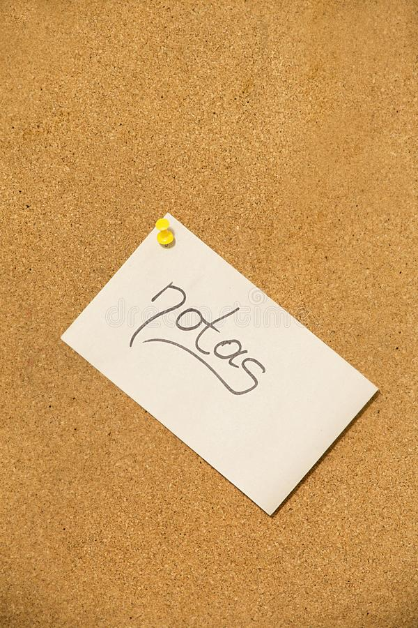 Nota kleverige nota met gele speld op cork raad stock foto's