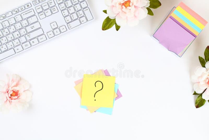 Nota multicolore degli autoadesivi con il punto interrogativo sul desktop bianco accanto ad una tazza di caffè e della tastiera fotografie stock libere da diritti