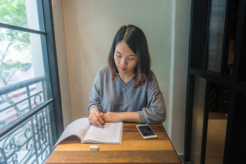 A nota nova da escrita do estudante, toma a nota, fazendo trabalhos de casa no livro foto de stock
