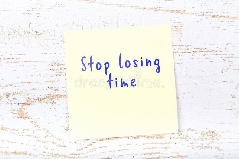 Nota pegajosa amarela com texto escrito à mão para parar de perder o tempo imagem de stock