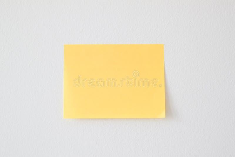 Nota pegajosa amarilla en blanco sobre la pared blanca fotos de archivo libres de regalías