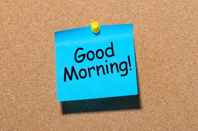 A nota pegajosa azul escreve o bom dia isolada no fundo da placa da cortiça imagem de stock royalty free