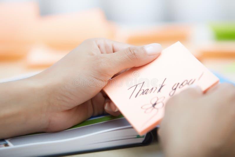 A nota pegajosa das terras arrendadas da mulher de negócios com agradece-lhe text fotos de stock royalty free