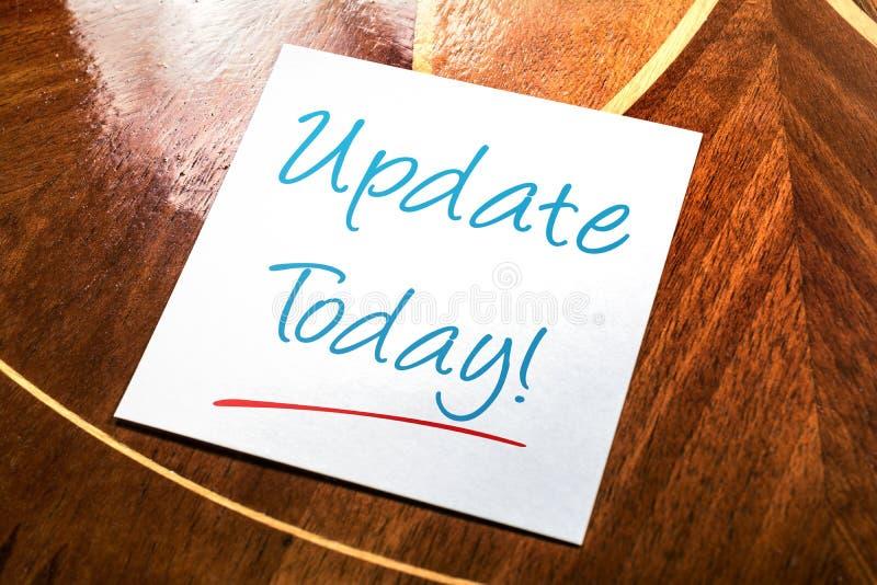 Nota pegajosa de la actualización para el hoy en el papel que miente en armario de madera foto de archivo libre de regalías