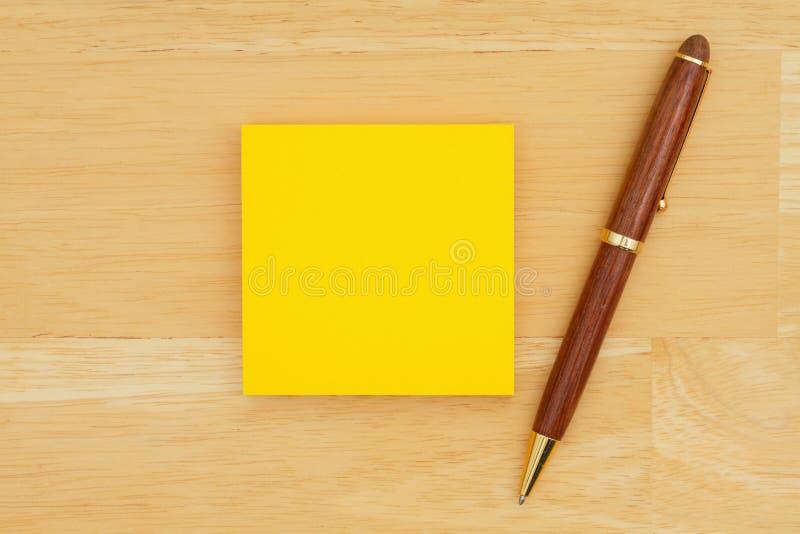 Nota pegajosa en blanco amarilla con una pluma en fondo de madera texturizado imagen de archivo libre de regalías