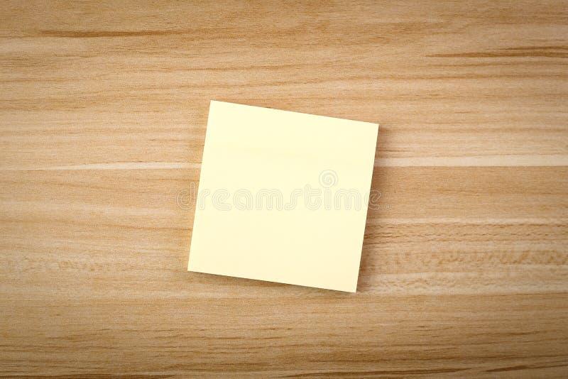 Nota pegajosa en blanco sobre la tabla de madera fotografía de archivo