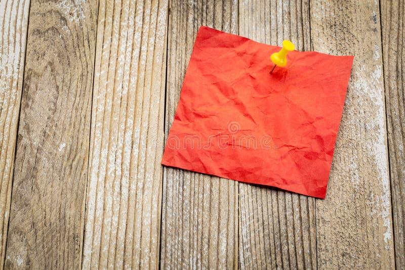 Nota pegajosa vermelha vazia na madeira do grunge imagem de stock