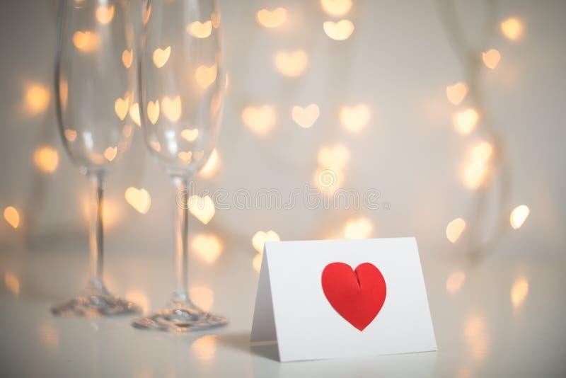 Nota romantica del messaggio con cuore rosso 3d su e champagne con i vetri e corde leggere leggiadramente con il bokeh del cuore  fotografie stock