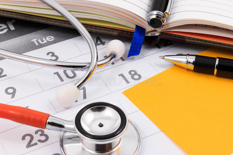 Nota sul calendario, appuntamento dello stetoscopio, della penna e della carta di medico fotografie stock