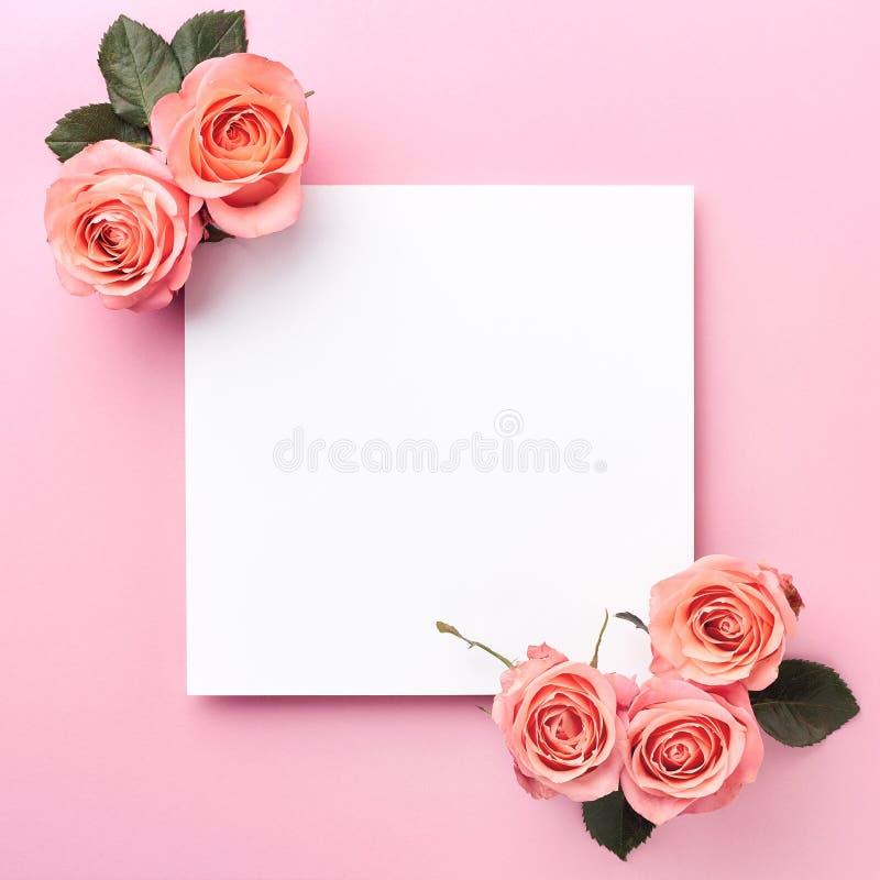 Nota y rosas del papel en blanco en fondo rosado fotografía de archivo