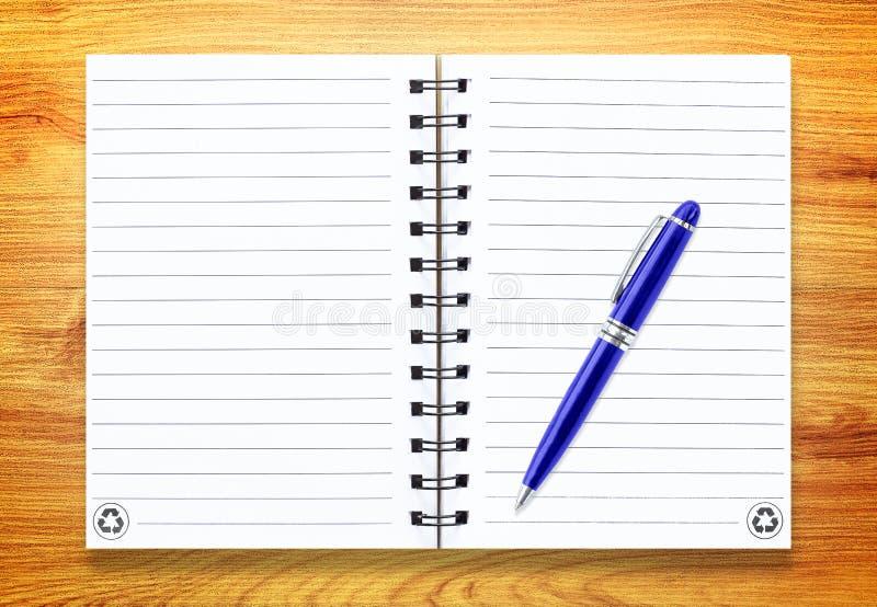 Notaboek met pen op hout stock afbeelding