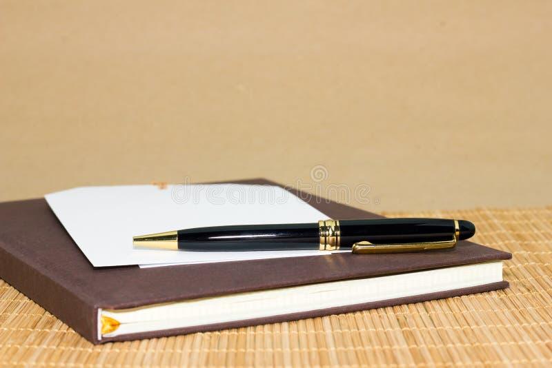Notadocument en zwarte pen op bruine achtergrond stock foto's