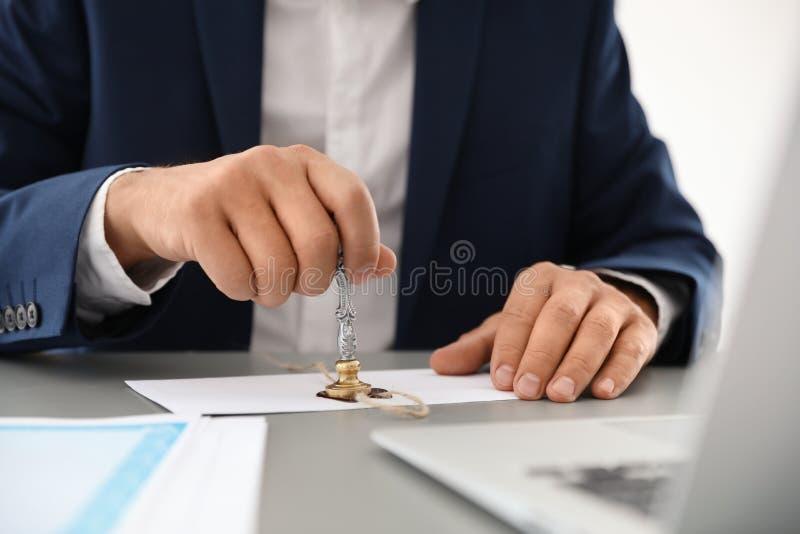 Notaire emboutissant le document au bureau dans le bureau photographie stock libre de droits
