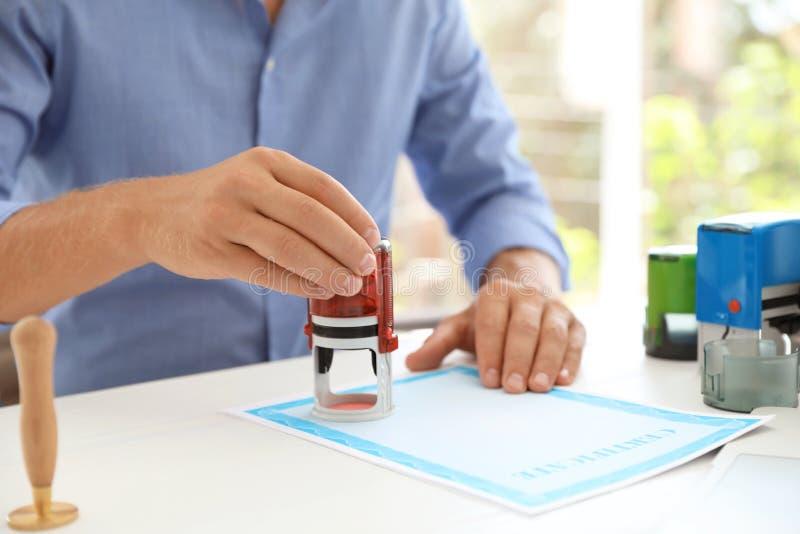 Notaire masculin emboutissant le document à la table images stock