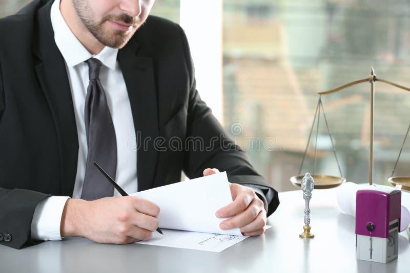 Notaire masculin travaillant avec des documents à la table dans le bureau, photo stock