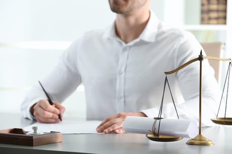Notaire masculin travaillant avec des documents à la table à l'intérieur photos libres de droits