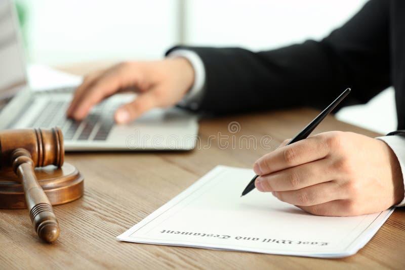 Notaire masculin travaillant avec les documents et l'ordinateur portable à la table photographie stock libre de droits