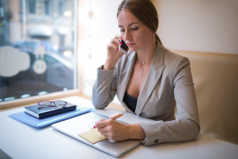 Notario de sexo femenino joven de la escritura del propietario de negocio en etiqueta engomada después del trabajo sobre el orden fotos de archivo