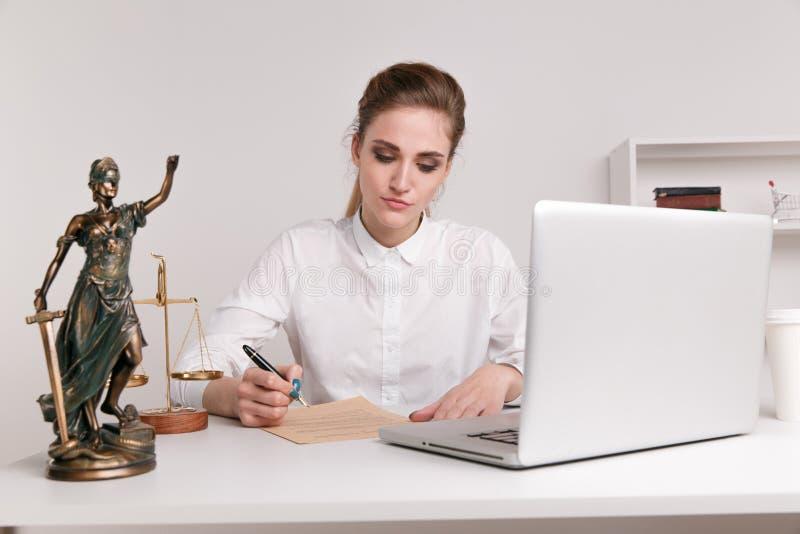 Notarisvrouw die op de documenten schrijven, die op haar computer typen stock afbeeldingen