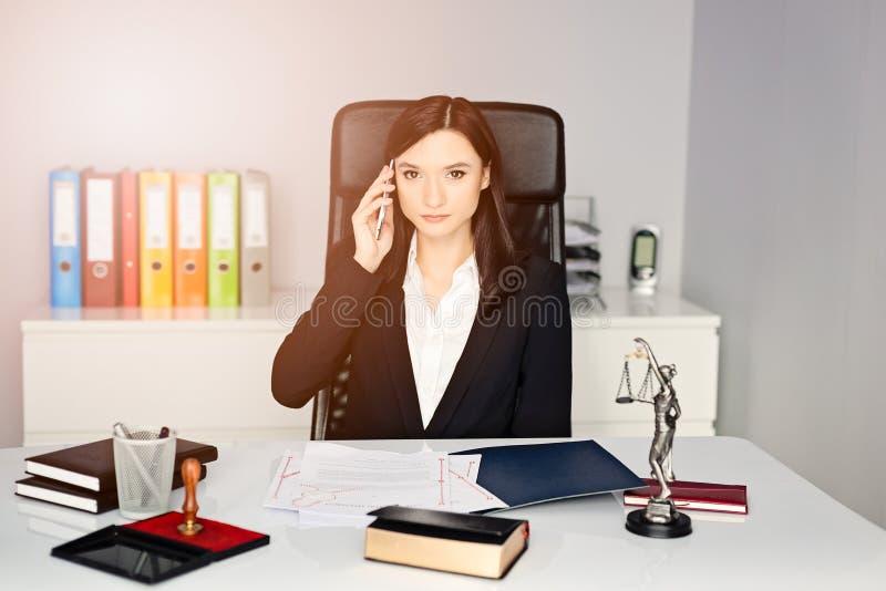 Notarius publicu Public som talar på mobiltelefonen i hennes kontor royaltyfri bild