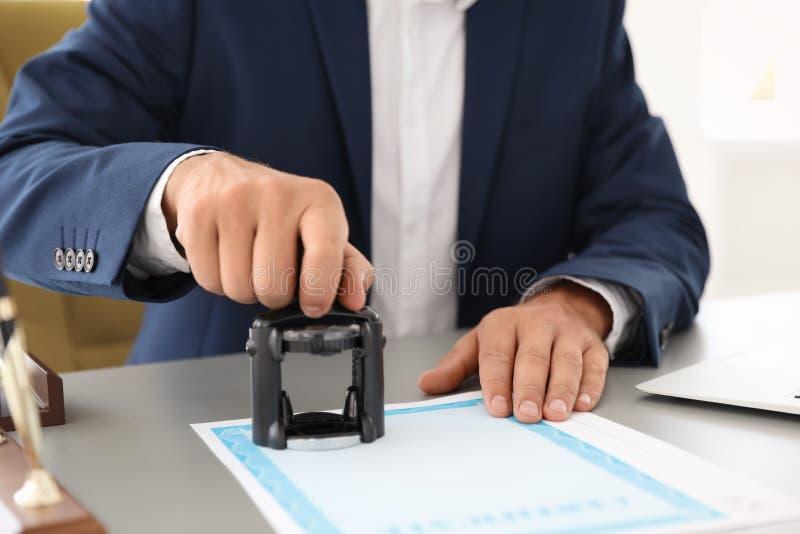 Notarius publicu som i regeringsställning stämplar dokumentet på skrivbordet royaltyfri foto