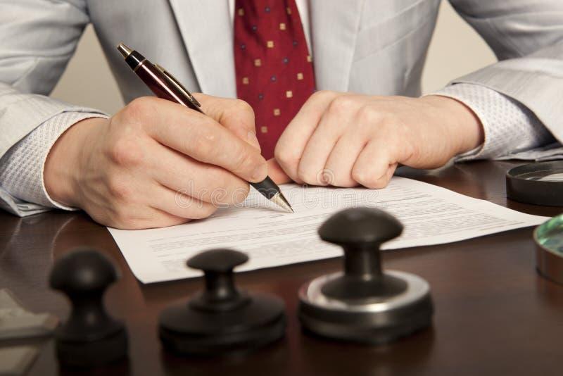 Notarius publicu undertecknar dokumenten från vårt kontor royaltyfri fotografi