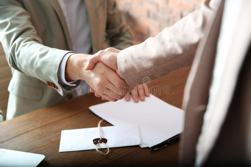 Notary and client shaking hands in office, closeup. Law and justice concept royalty free stock photography