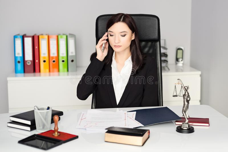 Notary Public talking on cellphone in her office. Brunette woman - Notary Public talking on cellphone in her office royalty free stock photo