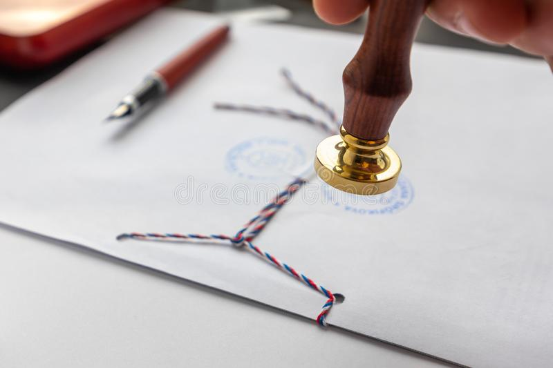 Notary public wax stamper. White envelope with brown wax seal, golden stamp. Responsive design mockup, flat lay. Still life with royalty free stock image