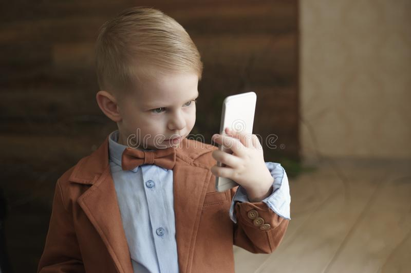 Boy with smartphone at home playing stock photography