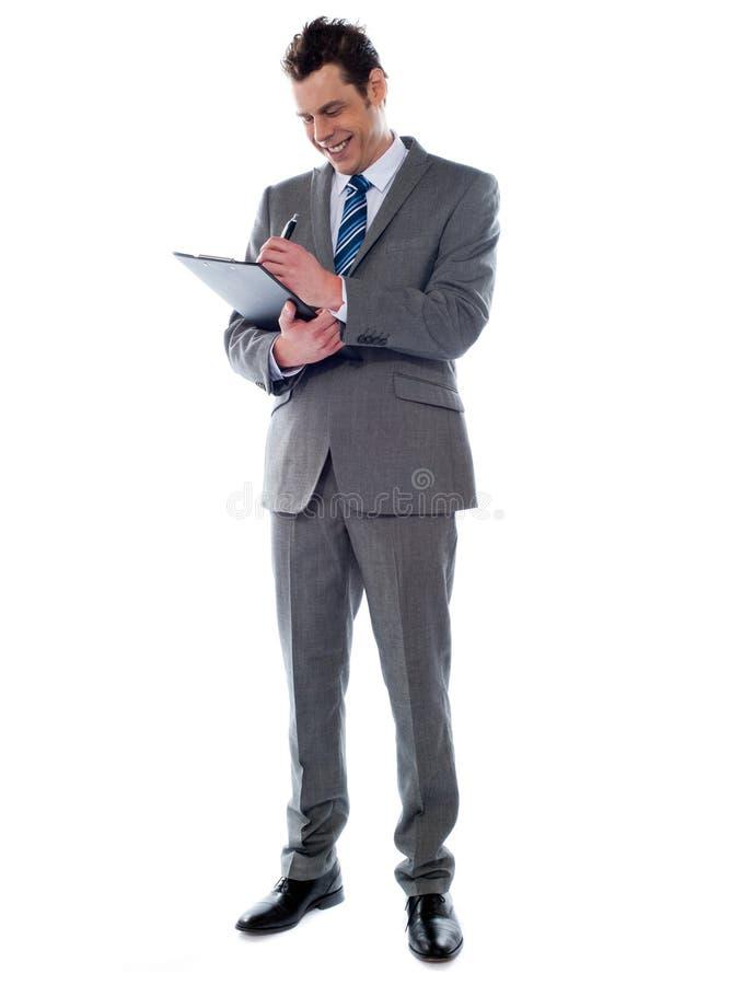 Notas acertadas de la escritura del hombre de negocios sobre el sujetapapeles imagen de archivo