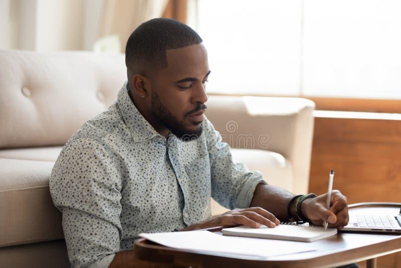 Notas africanas serias de la escritura del estudiante que estudian en casa con el ordenador portátil fotografía de archivo