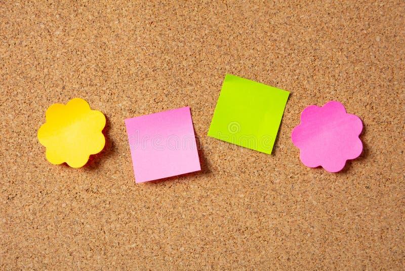 Notas coloridas pegajosas nas formas da flor e do quadrado, isoladas, espaço da cópia no fundo da cortiça fotografia de stock