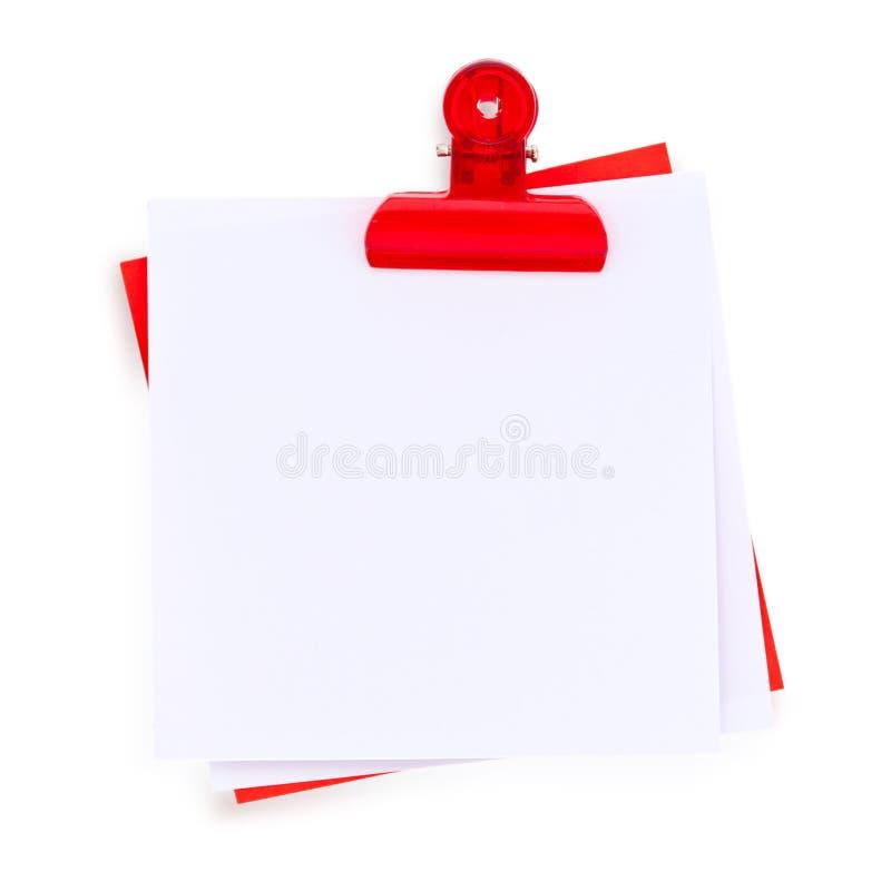 Notas con un clip rojo imagenes de archivo