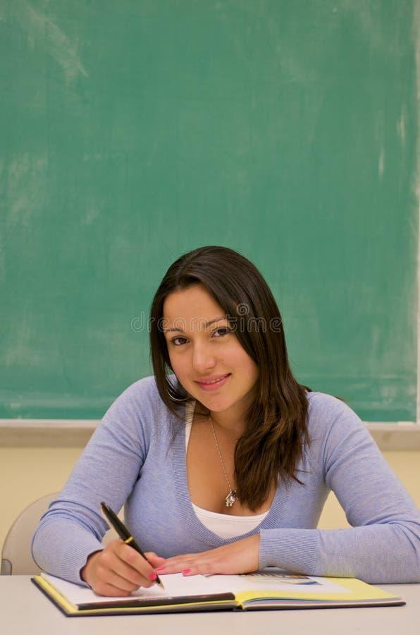 Notas da escrita do estudante na sala de aula imagem de stock royalty free