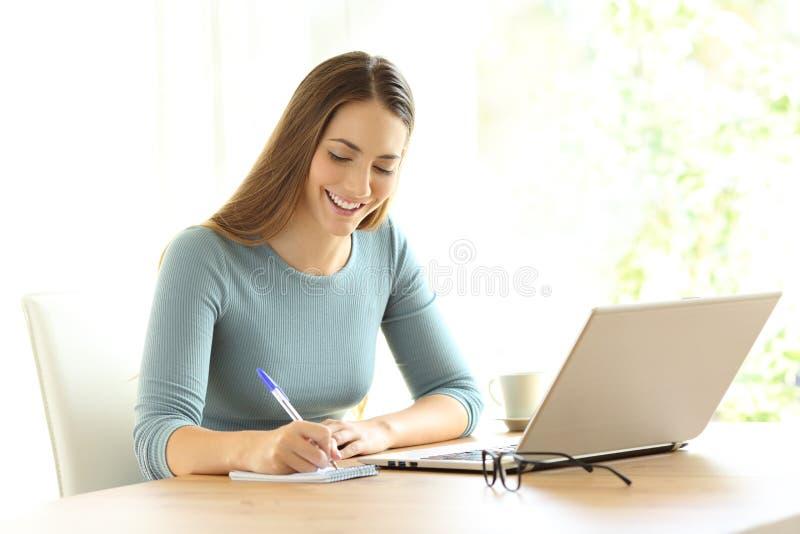 Notas da escrita da mulher ao lado de um portátil em casa fotografia de stock