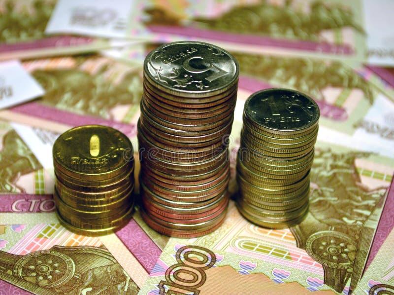 Notas de banco e moedas dos rublos do russo foto de stock