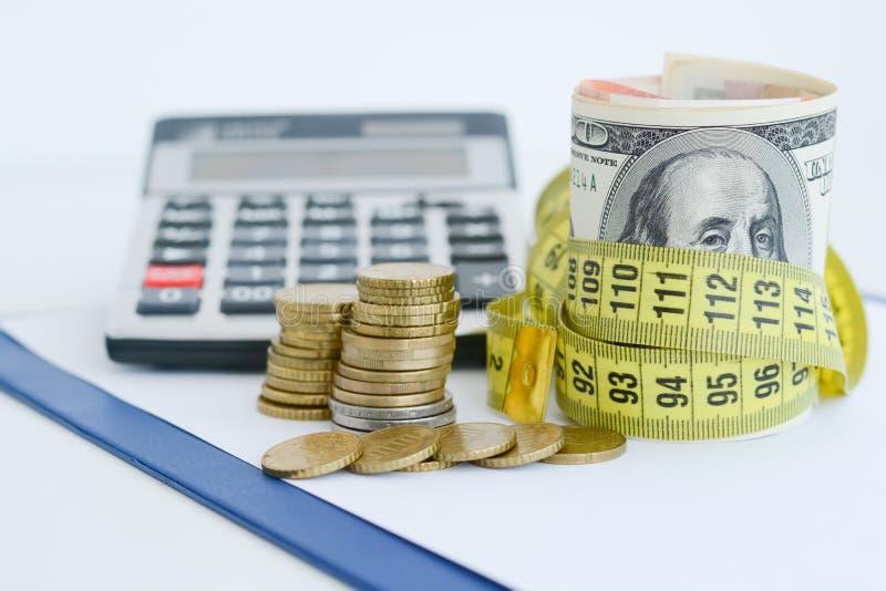 Notas de dólar amarradas acima com a fita de medição amarela que sugere a medida da situação financeira fotos de stock